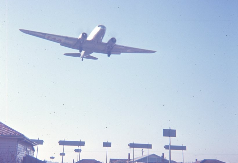 Click to view gallery of images. Photo supplied by Lindsay Walker of a TAA DC3 landing Essendon Airport from East over 'Ladder of Lights' Pascoe Vale 1962
